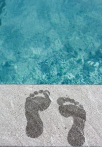 1118976-two-wet-foot-steps-by-swimming-pool